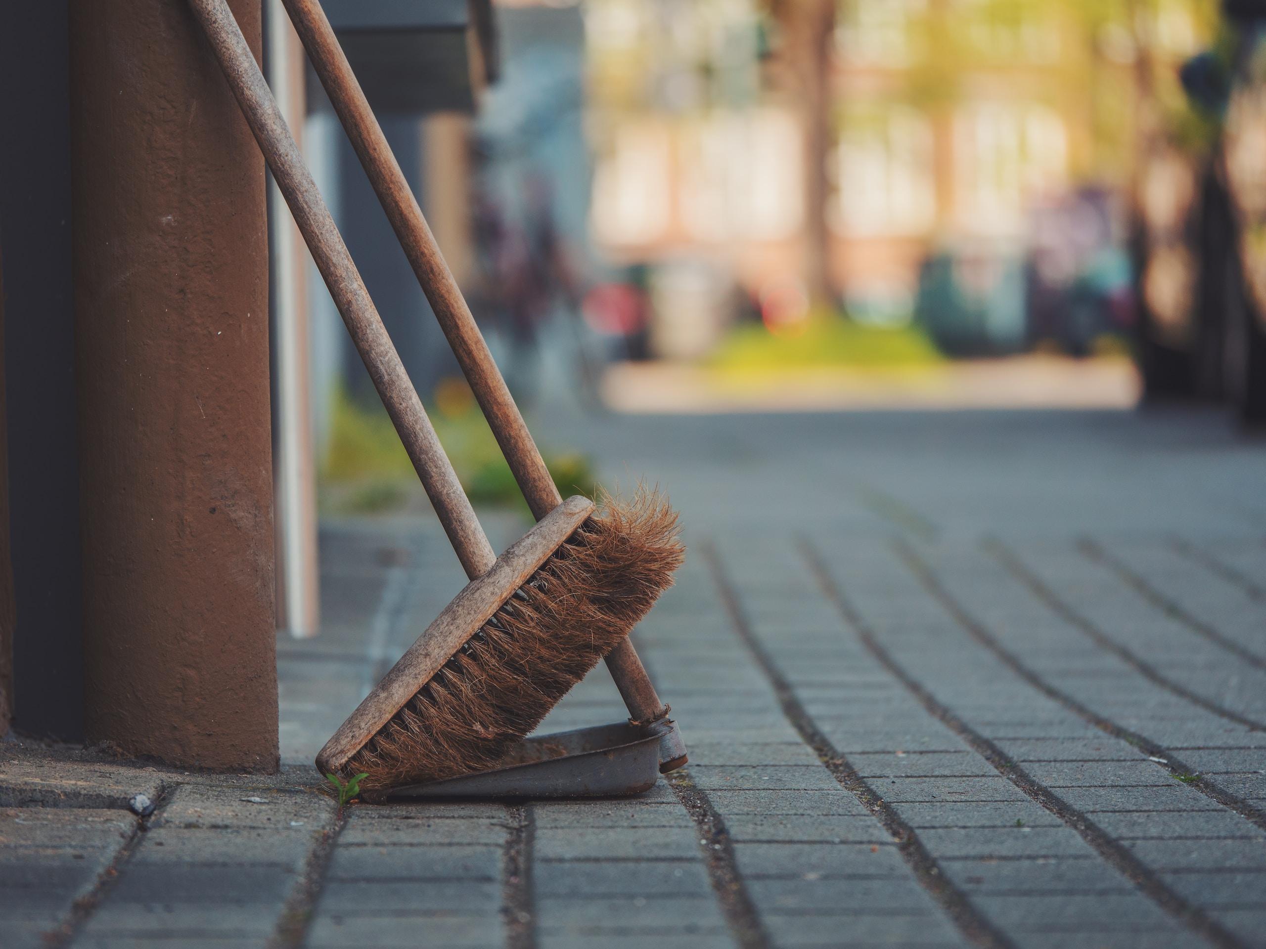 brown push broom on dust pan