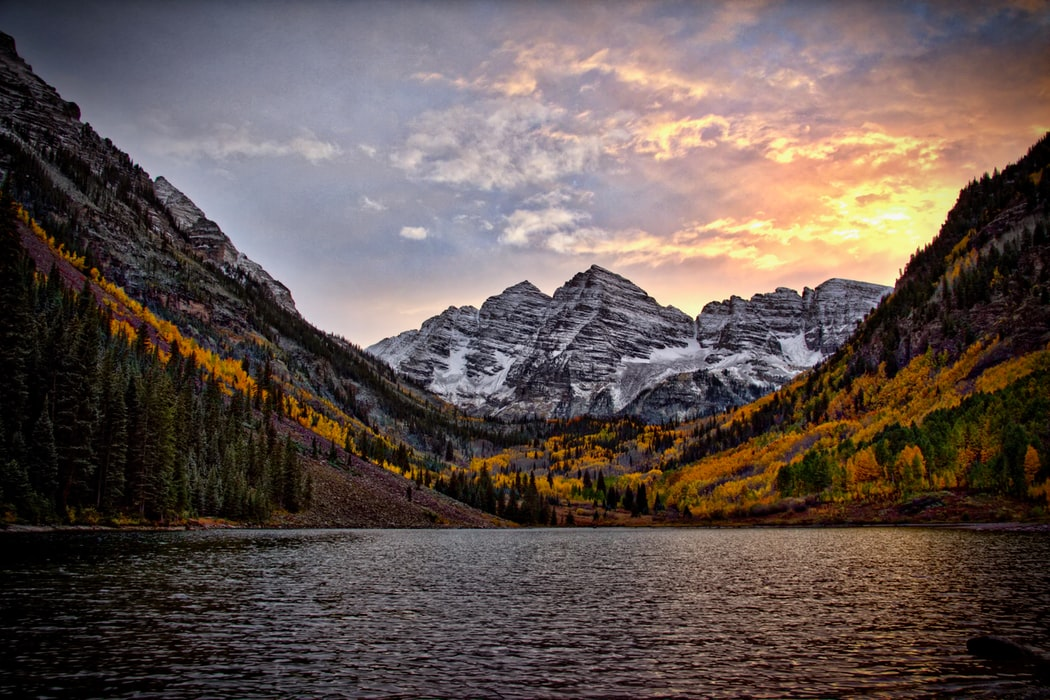 Colorado's lake at sunset with snow-capped mountains and fir tress in the distance