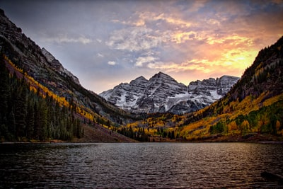 body of water across the mountain during sunset colorado teams background