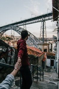 man and woman holding hands standing on stairs near bridge during daytime