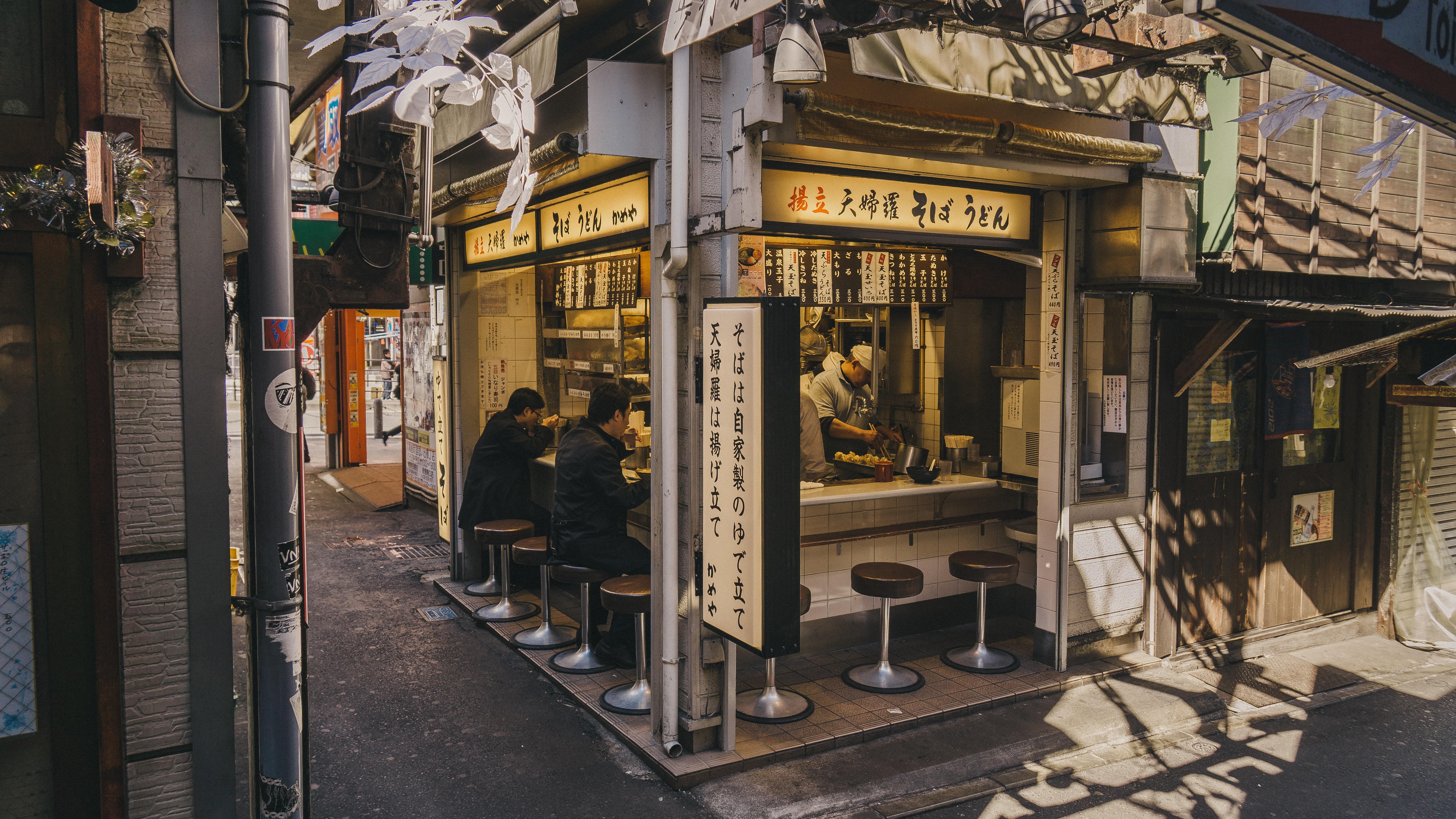 people eating inside stall beside street