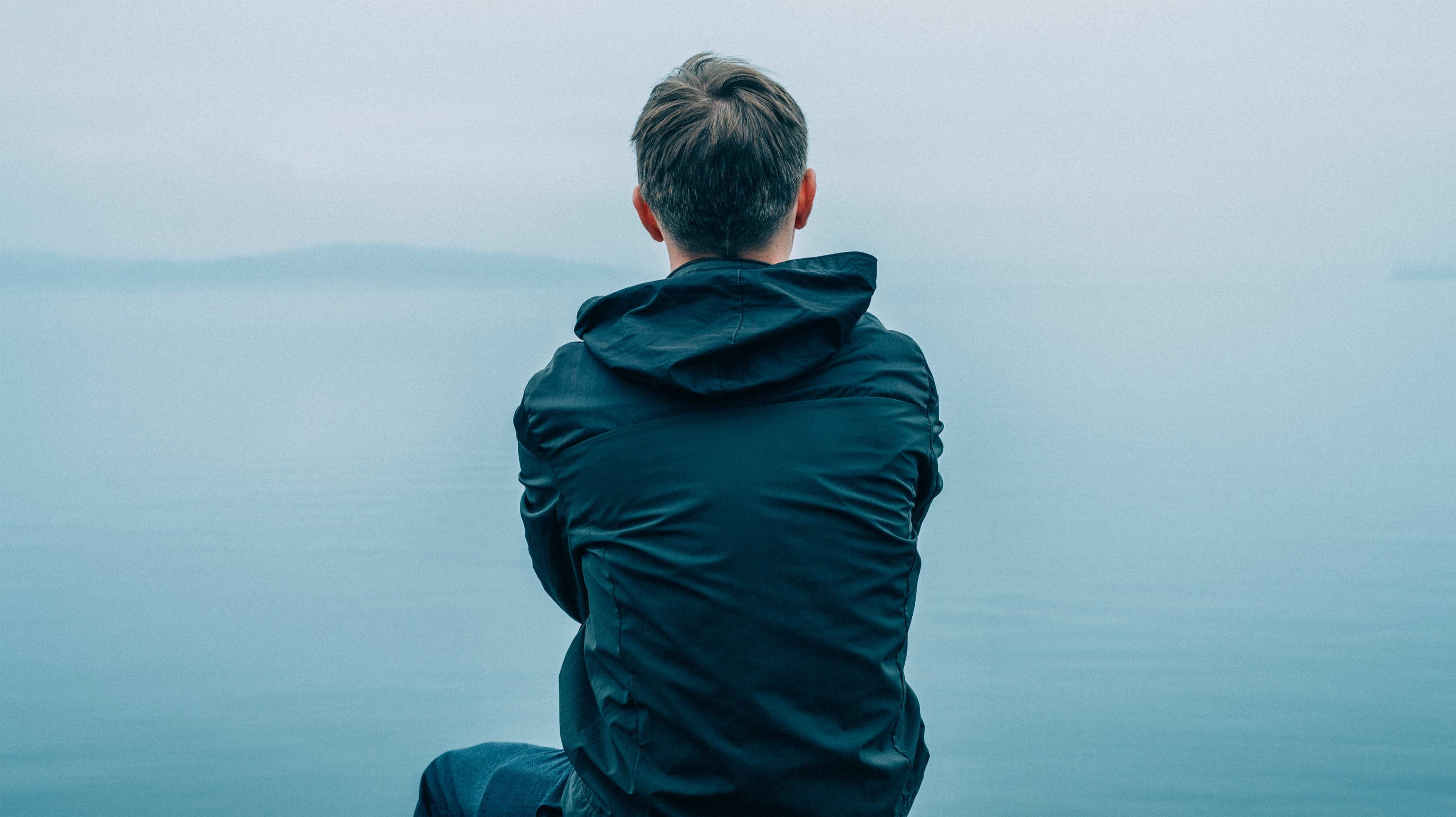 man in black hoodie sitting in front of ocean