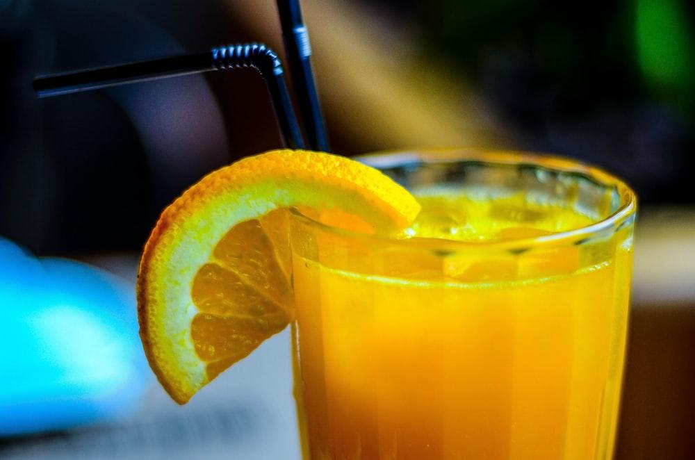 orange juice in drinking glass with slice orange fruit garnish