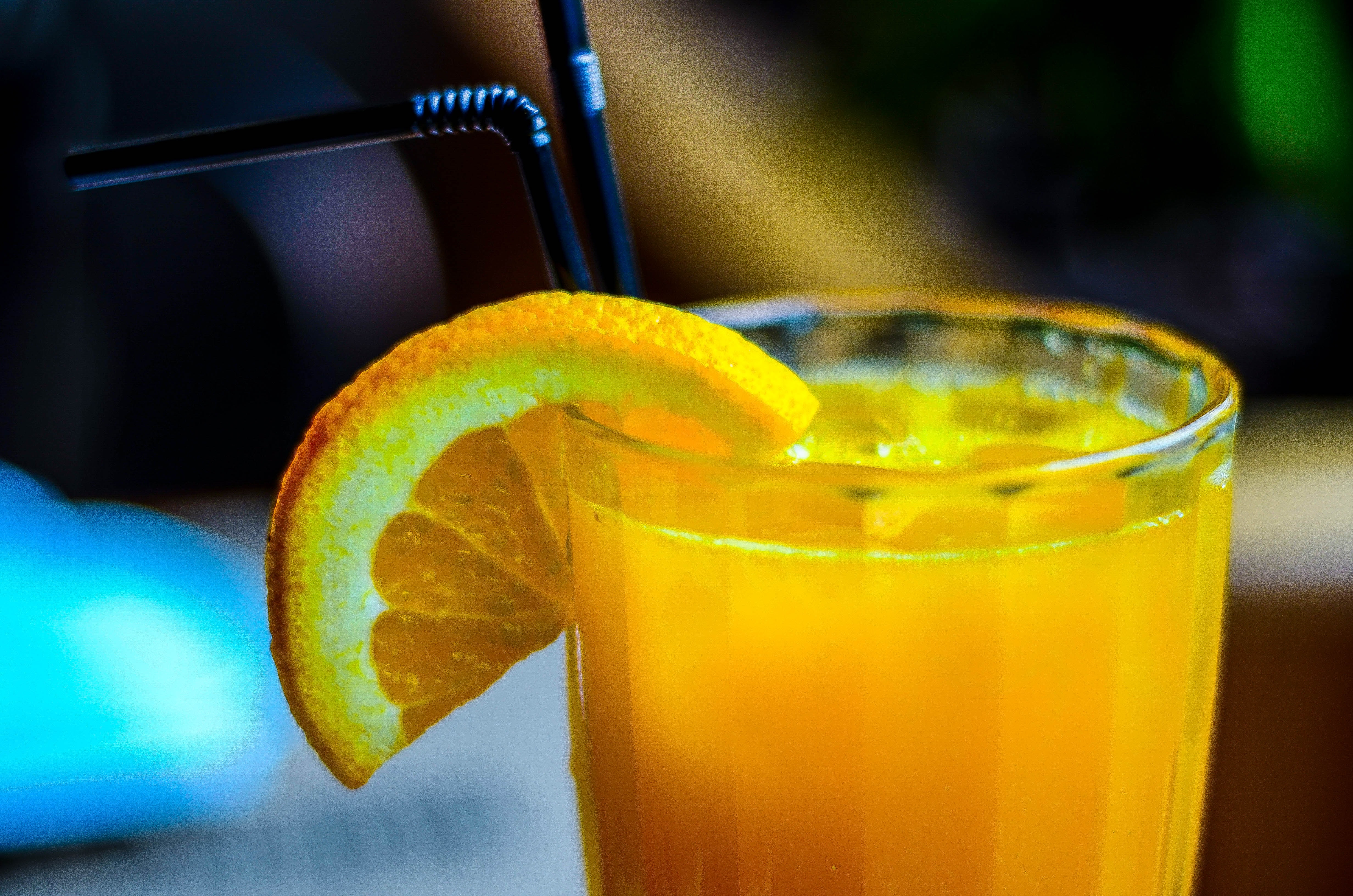 orange juice in drinking glass with slice orange fruit garnish