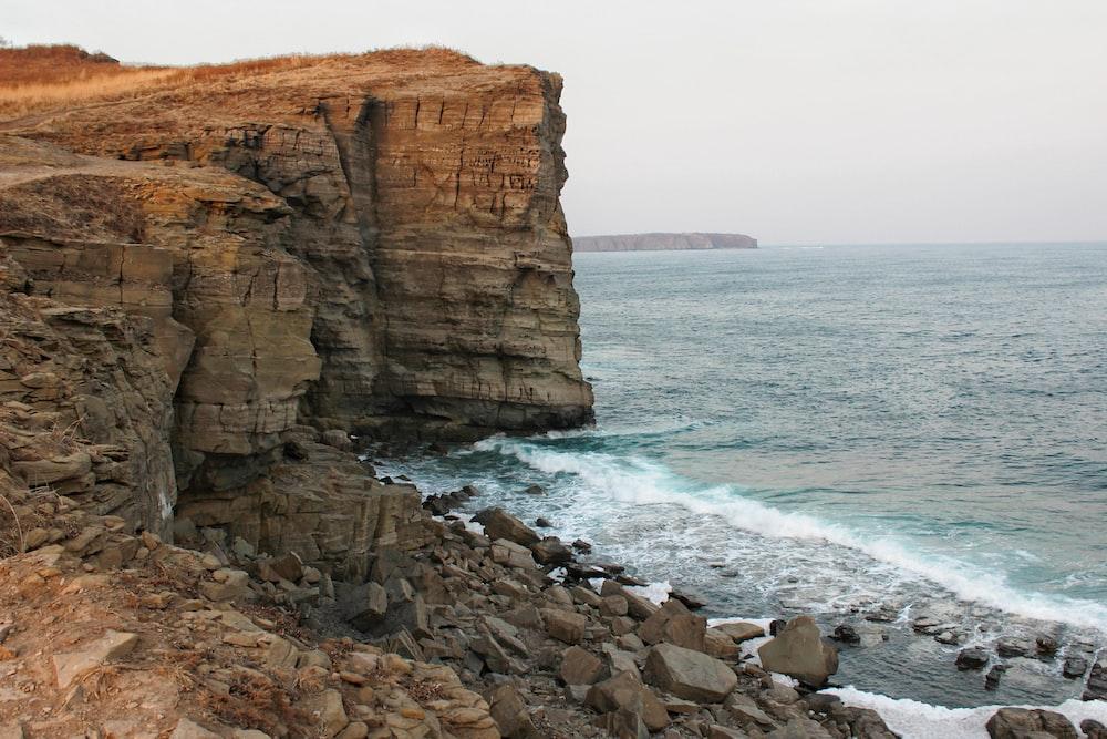rocky mountain on seashore during daytime