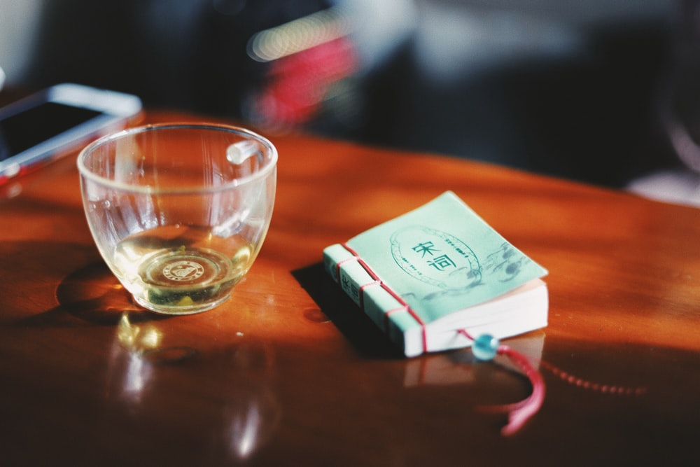 clear glass cup near sticky note on table