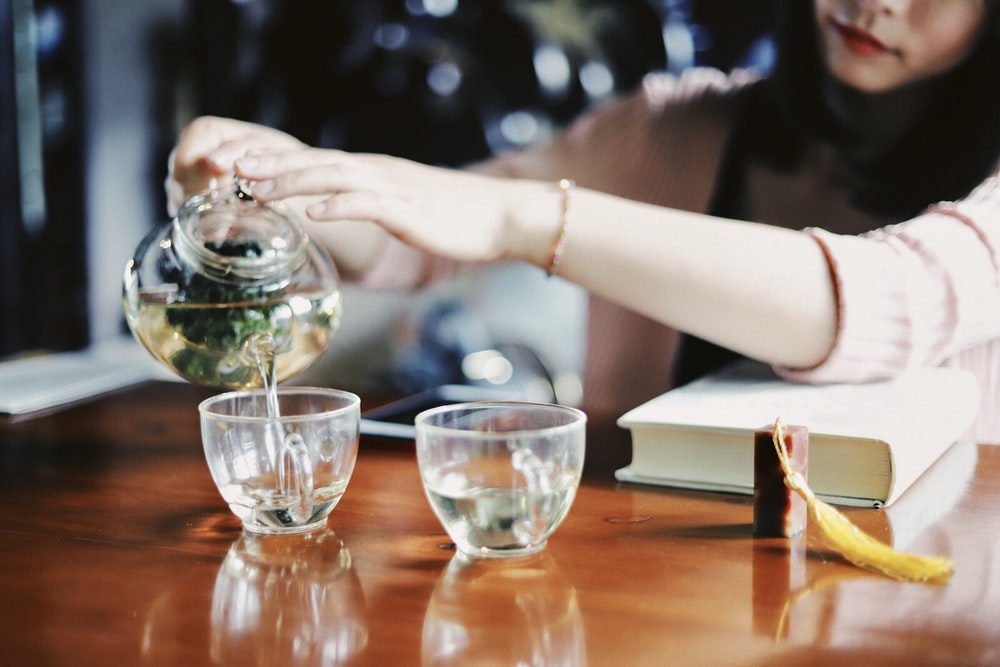 woman pouring tea on cups