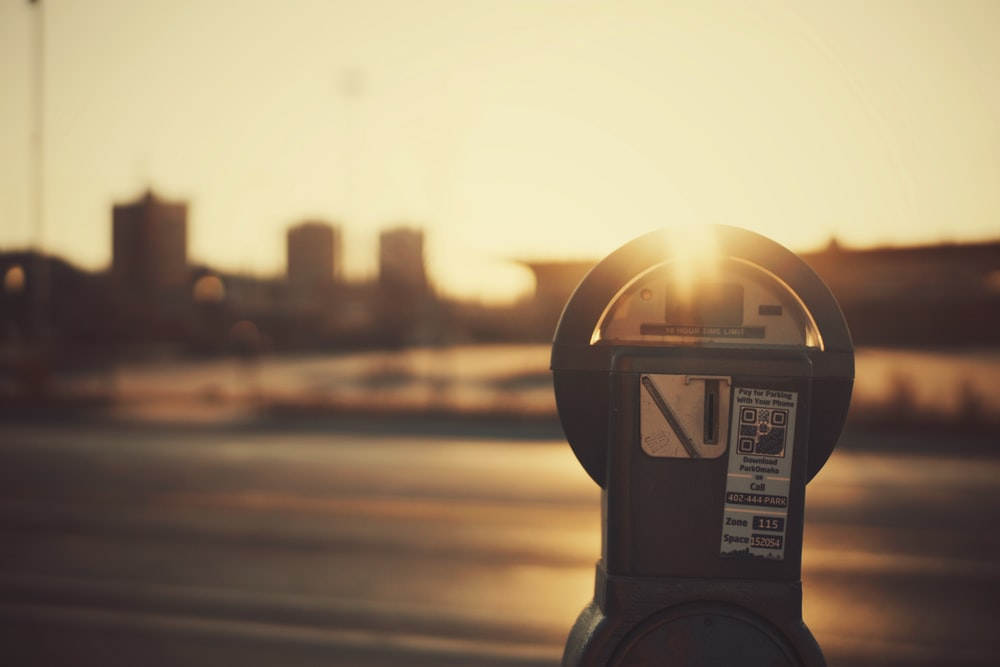 shallow depth of field photo of gray coin-operated parking meter