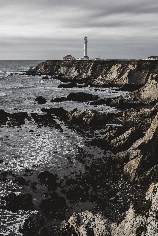 white lighthouse on cliff under gray sky