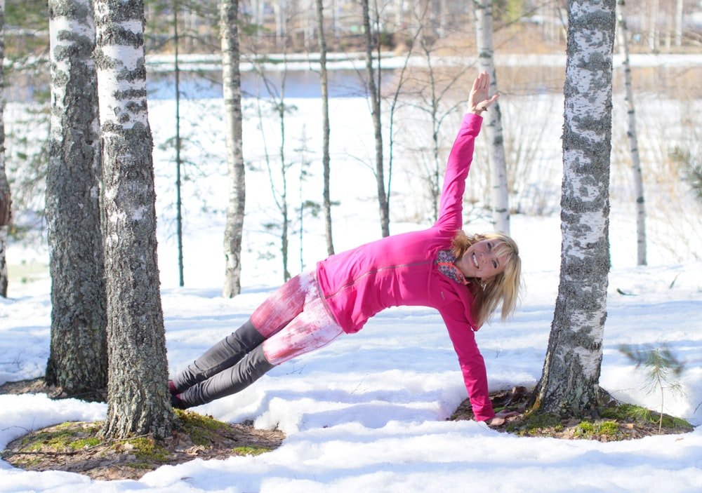 woman doing exercise outdoor in beside trees