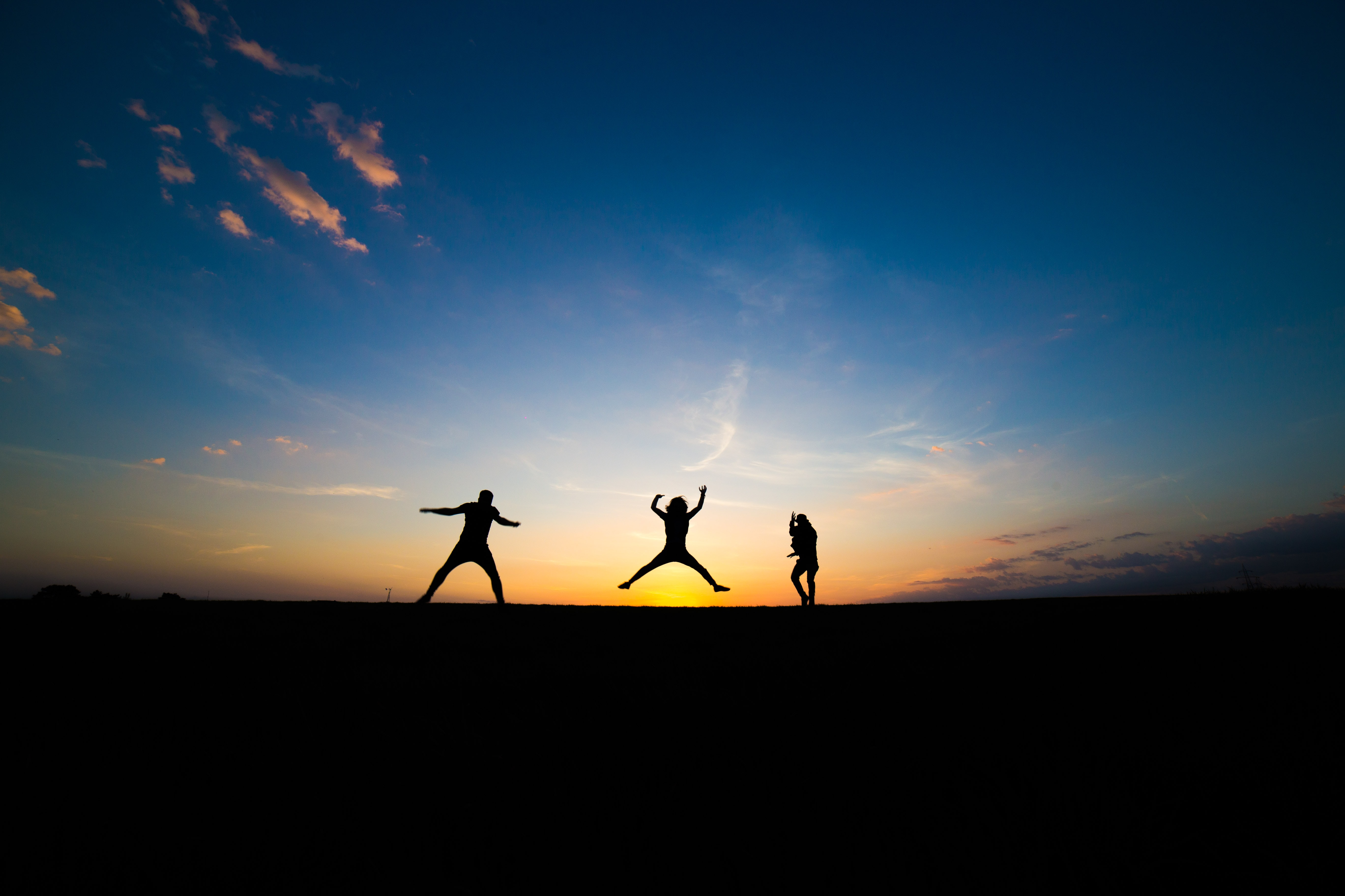 silhouette of three person jumping