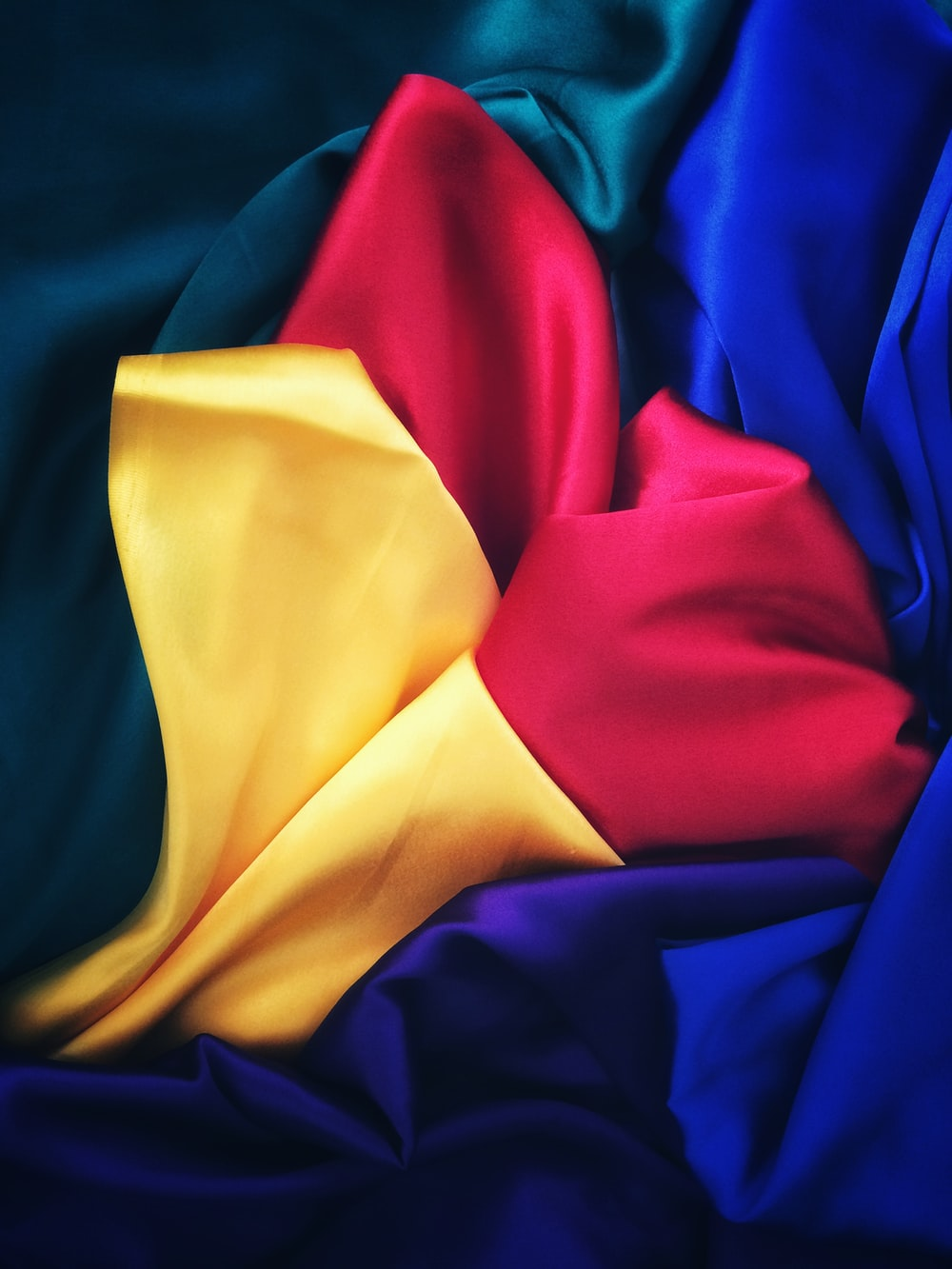 photo of red, yellow, blue and green silk cloths