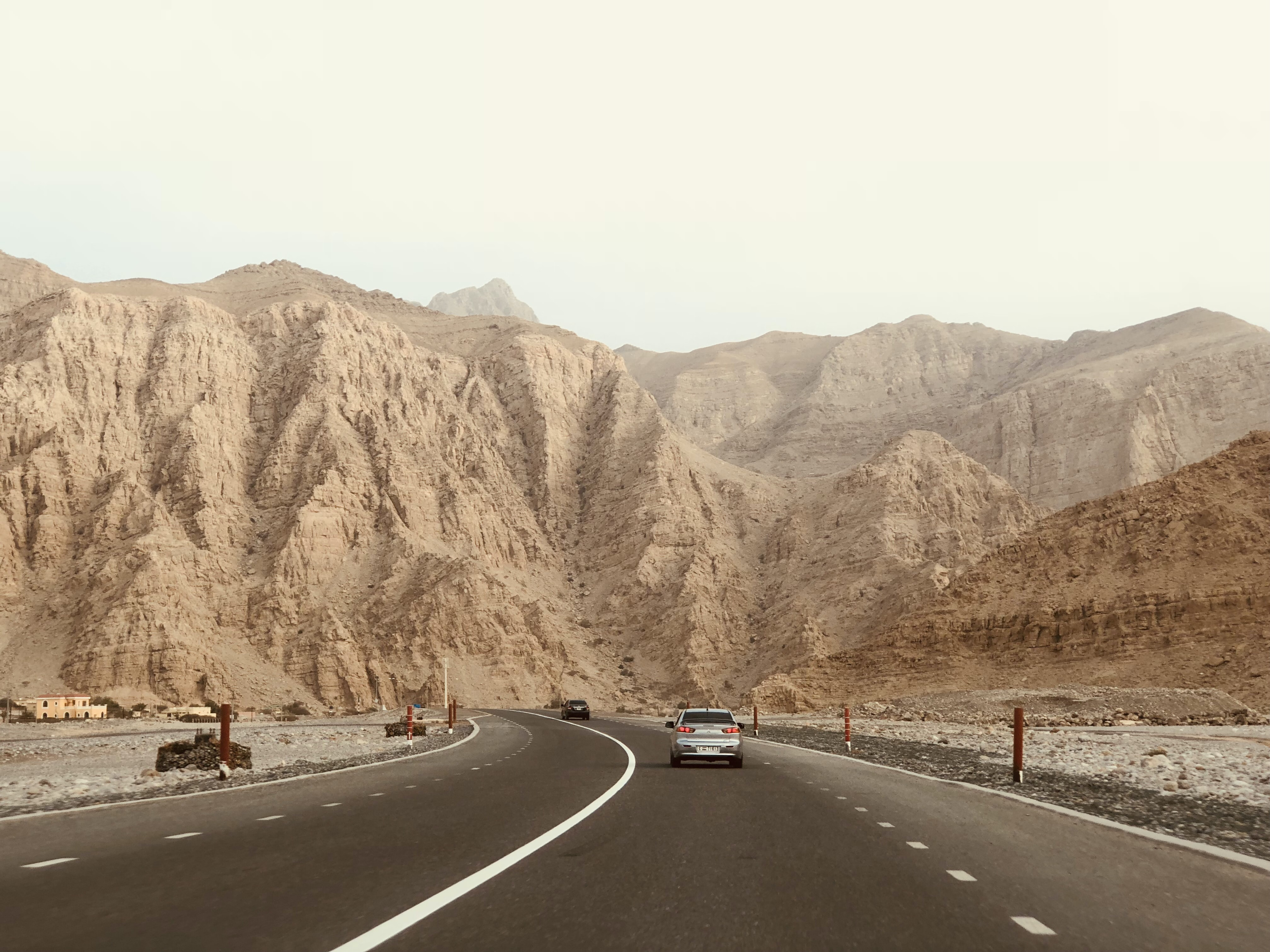 two vehicles on concrete highways near on mountains