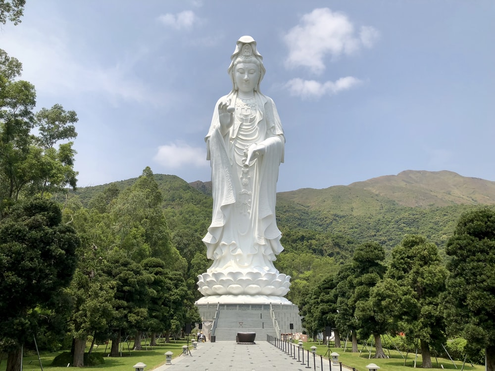 woman concrete statue beside mountains
