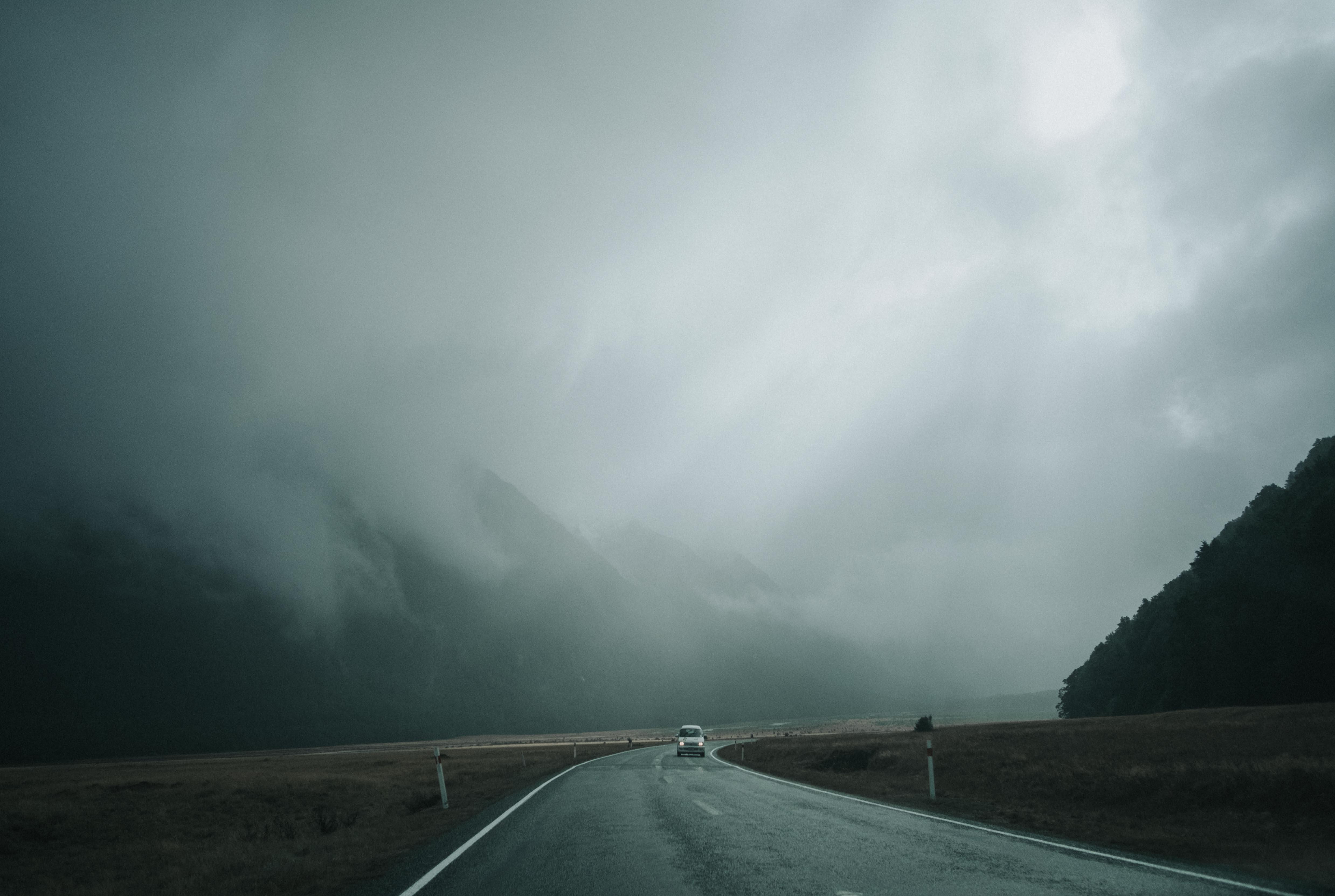 vehicle on asphalt road under gray cloudy sky