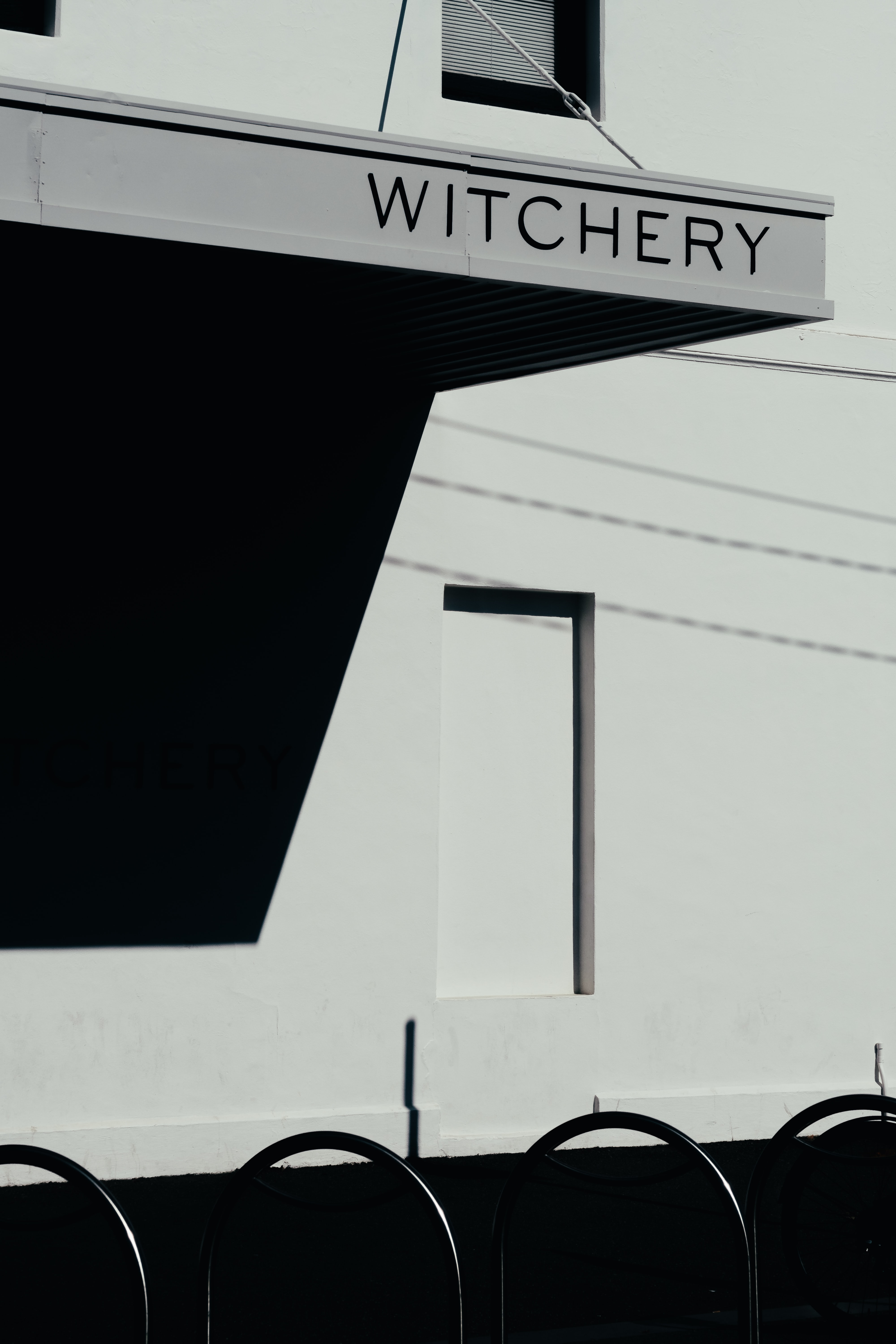 grayscale photography of Witchery signage
