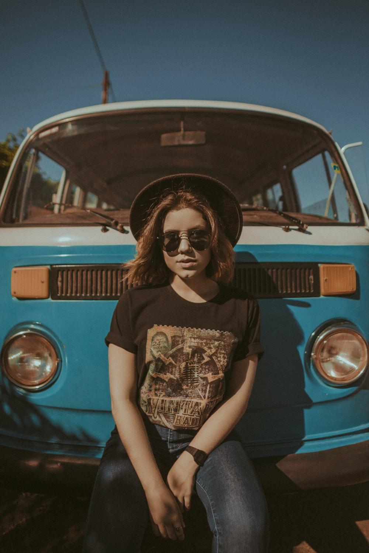 woman sitting on blue vehicle's bumper