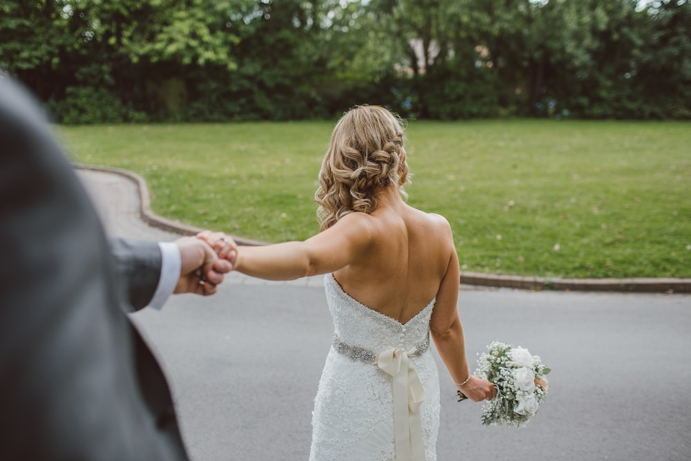 bride in backless wedding gown holding bouquet while holding grooms hand from behind