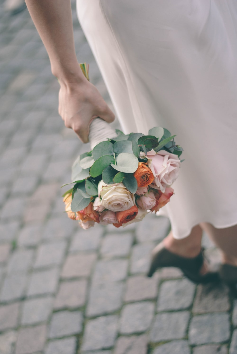person holding flower arrangement
