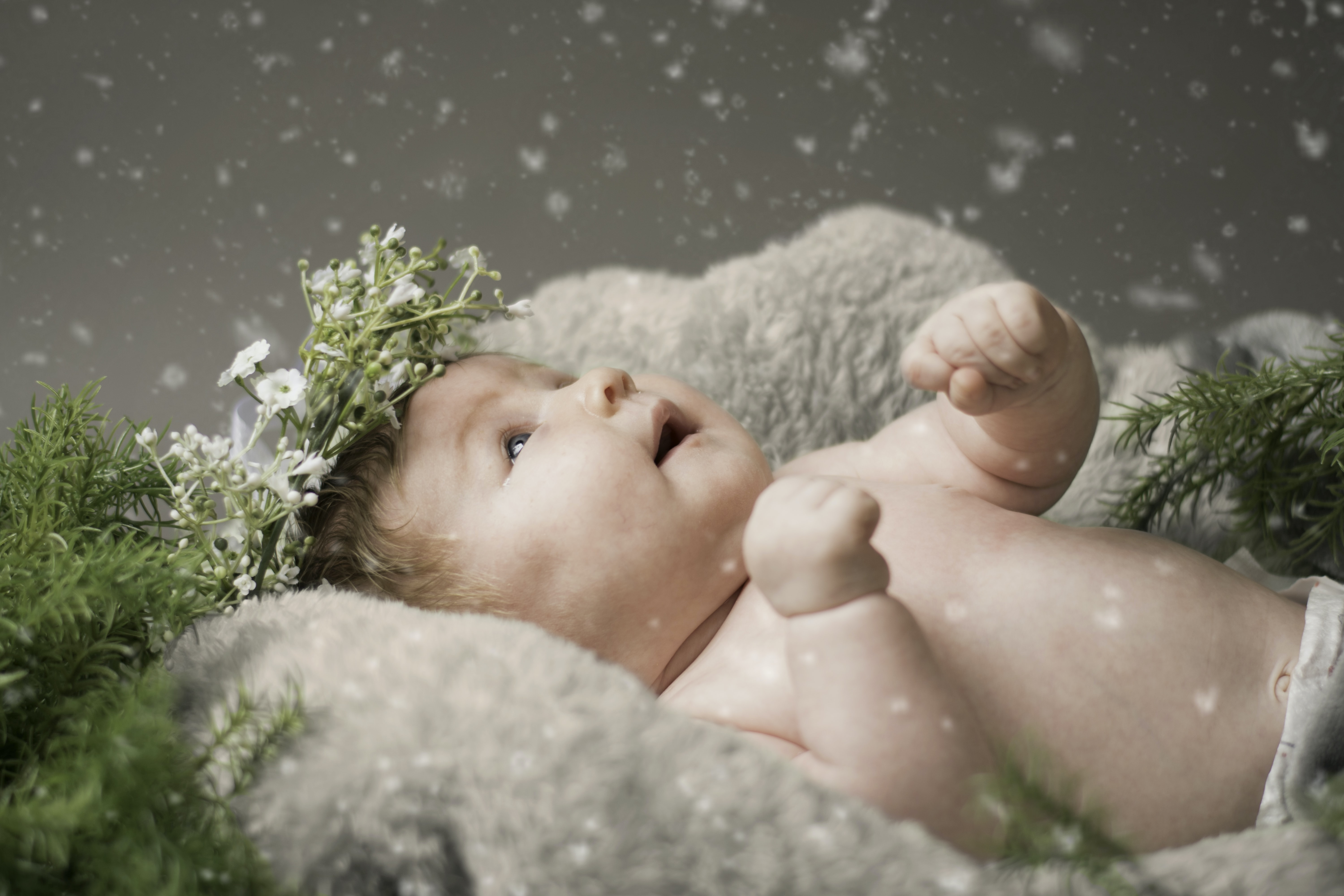 baby lying on gray textile