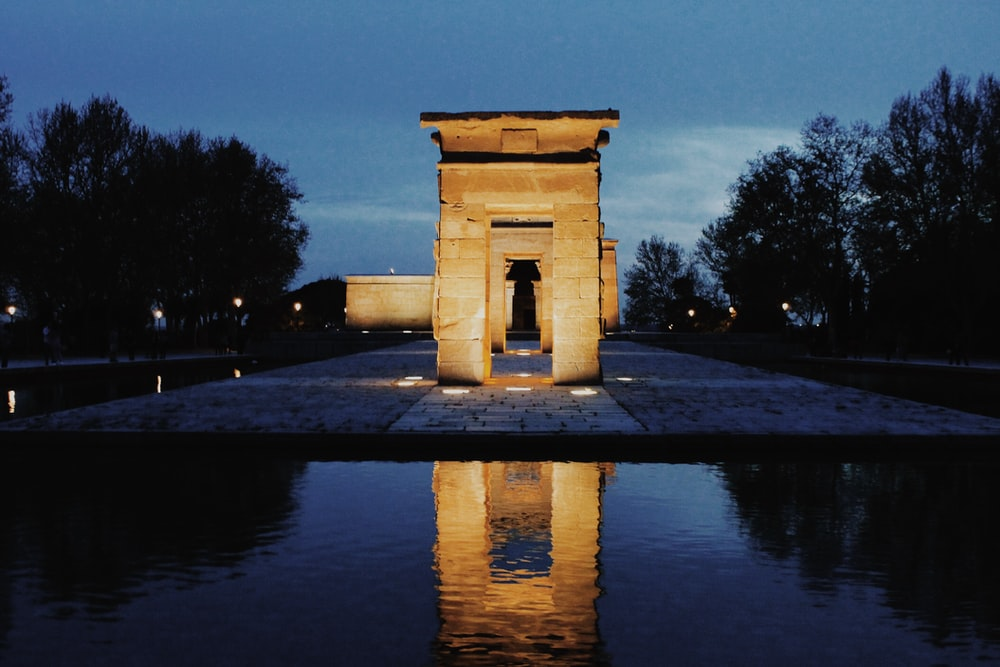 gray arch with lights in middle of water on park