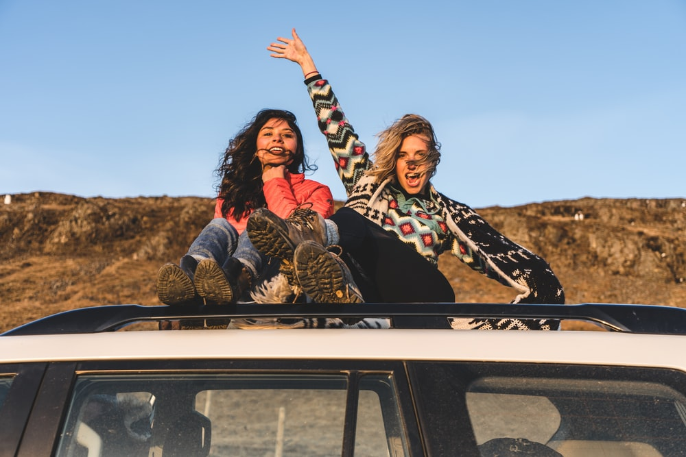 two woman sitting on top of white vehicle under blue sky during daytime