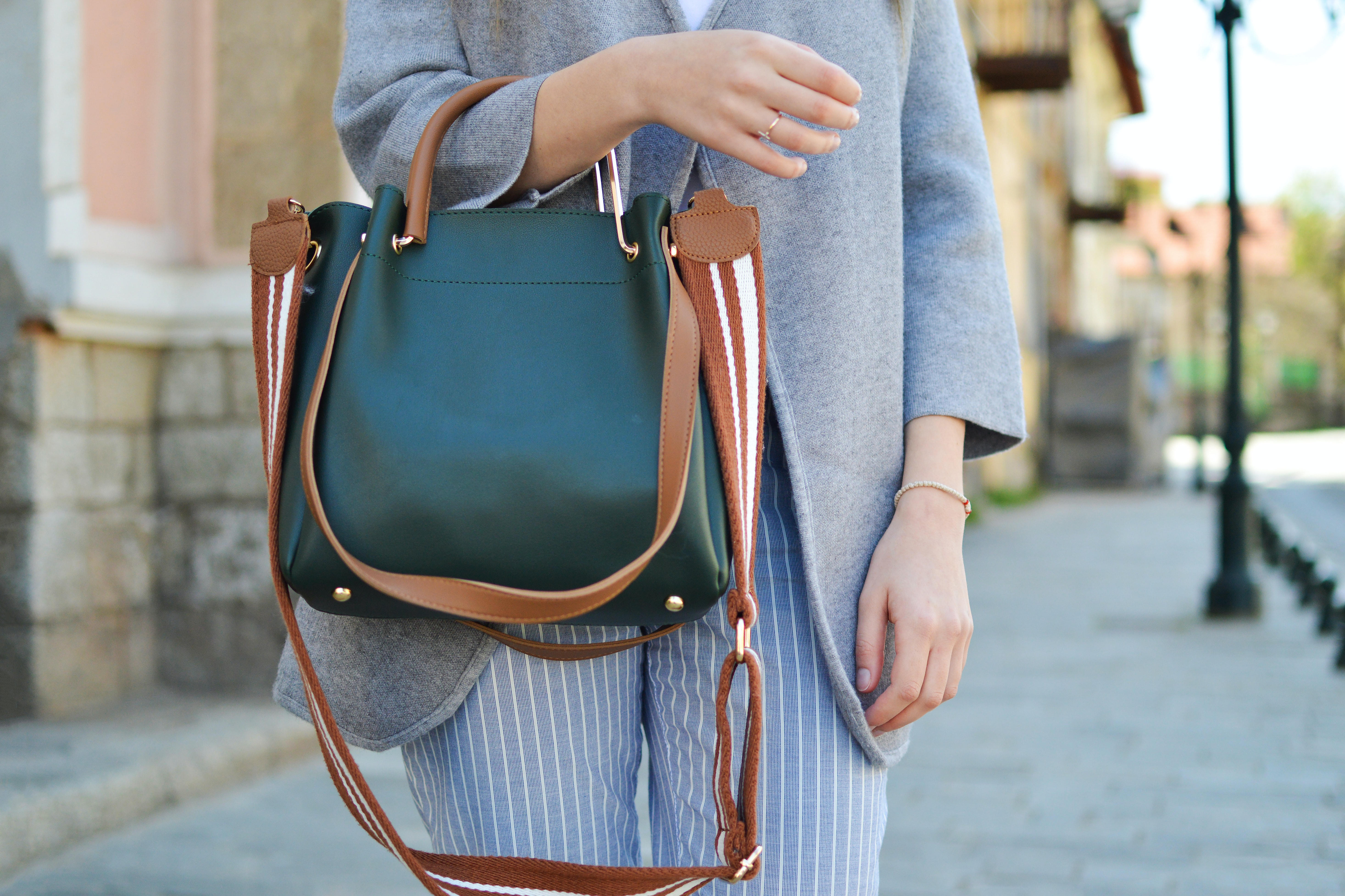women standing while carrying green and brown leather 2-way shoulder bag