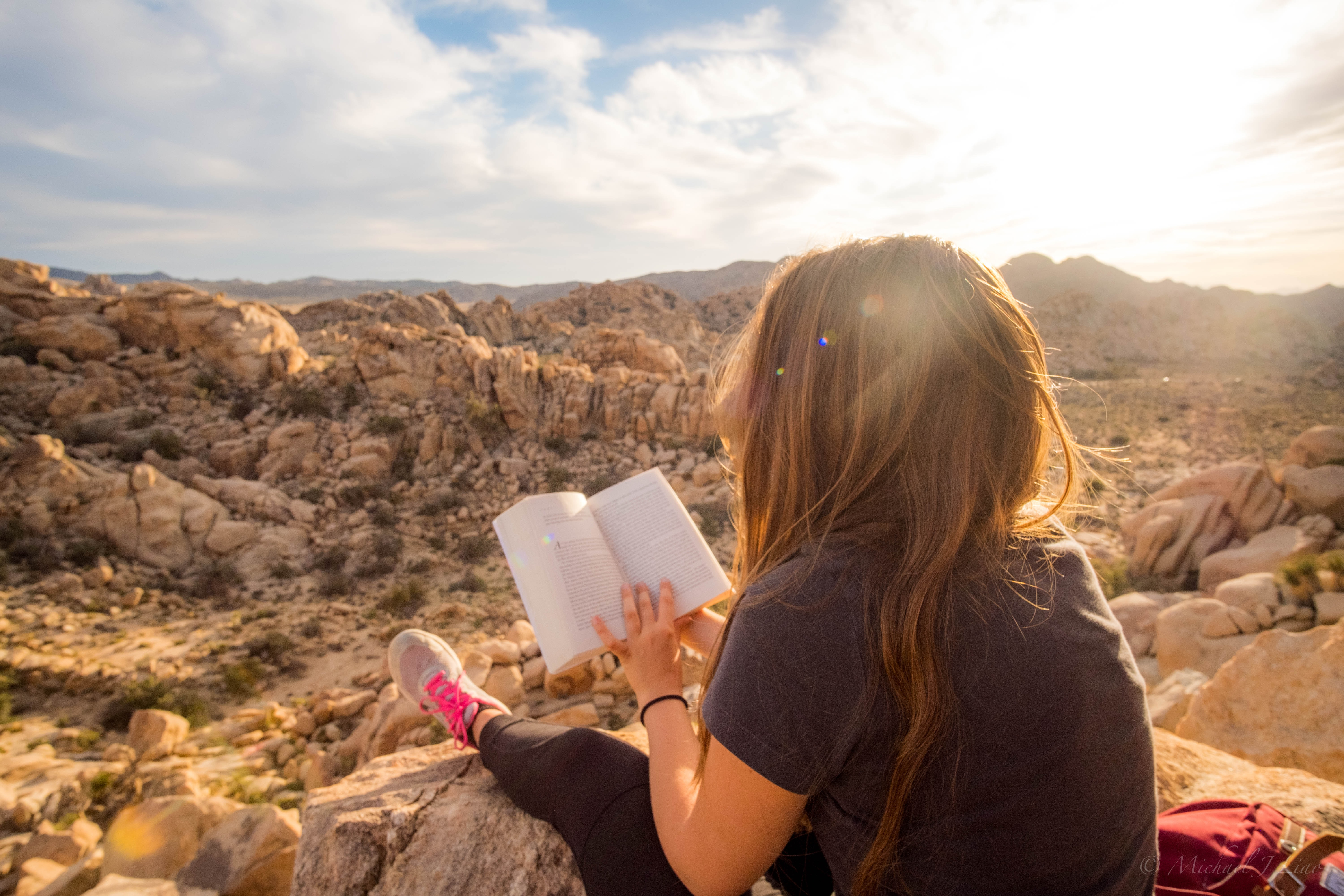 woman sitting on rock formation while reading book