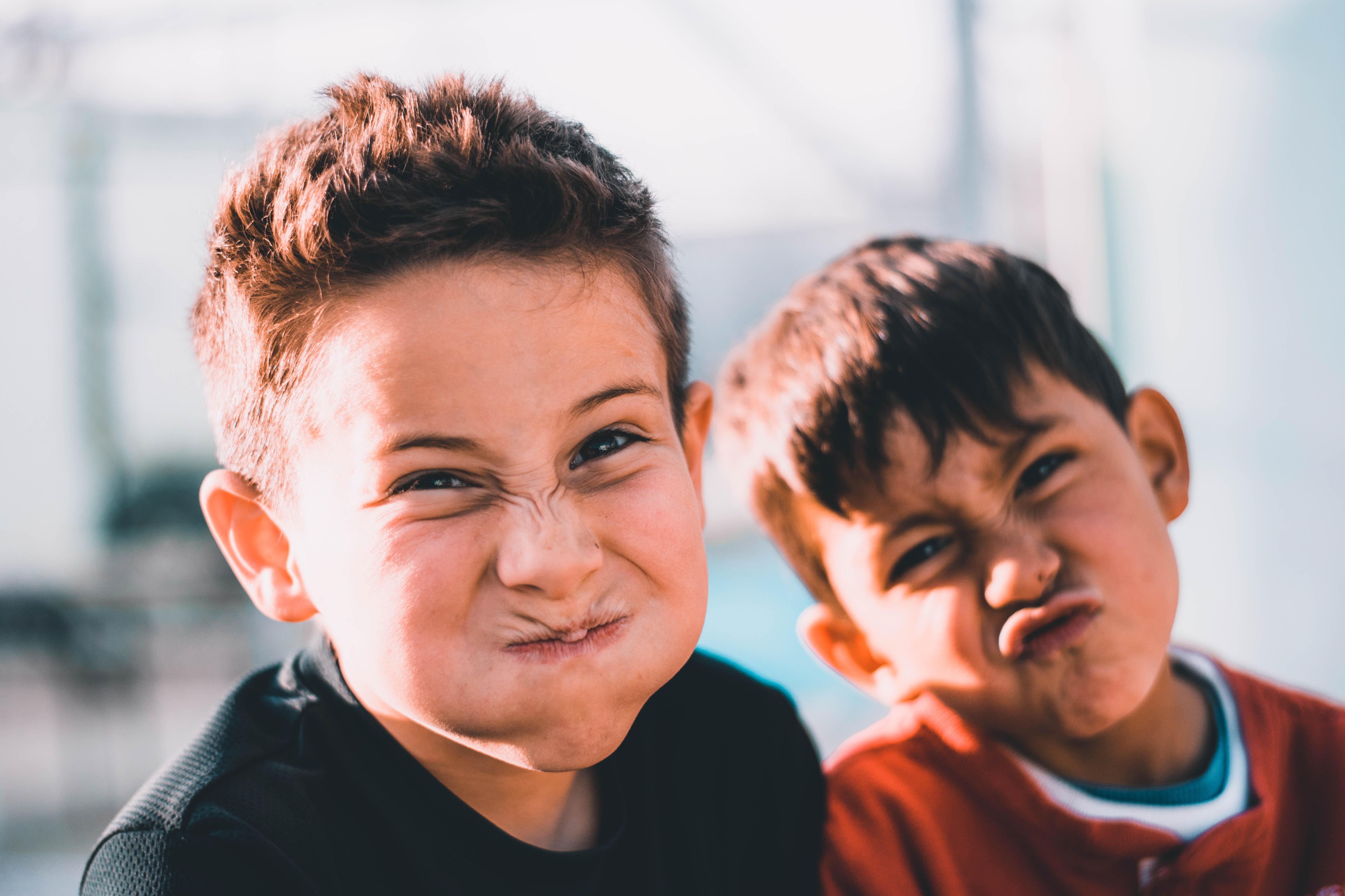 shallow focus photography of two boys doing wacky faces