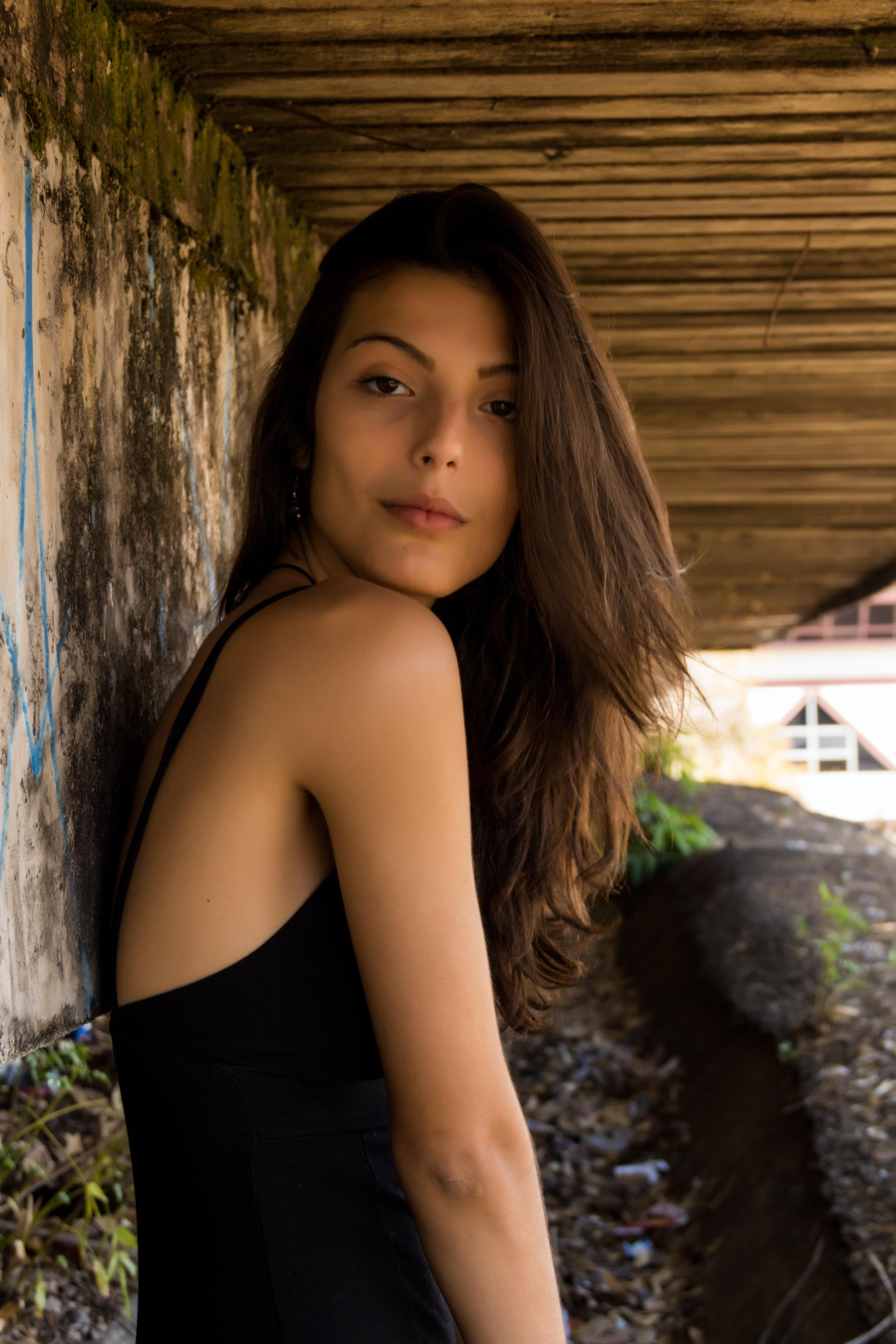 woman wearing black cami top leaning on wall under boardwalk