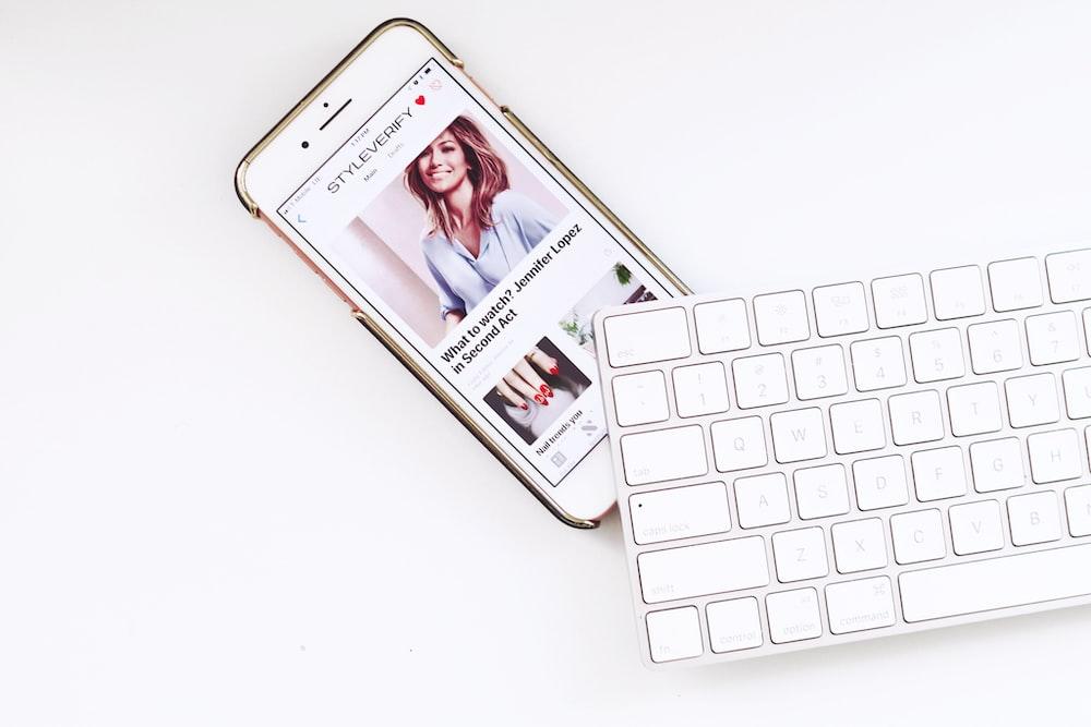 white iPhone under white Apple Magic Keyboard