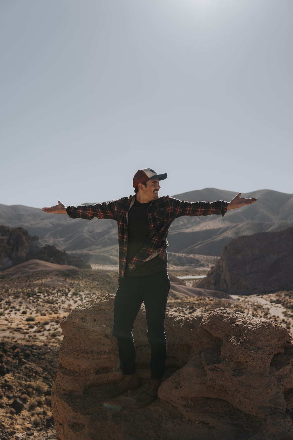 man wide arms open with mountain background