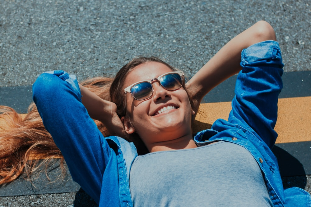 smiling woman lying on concrete pavement