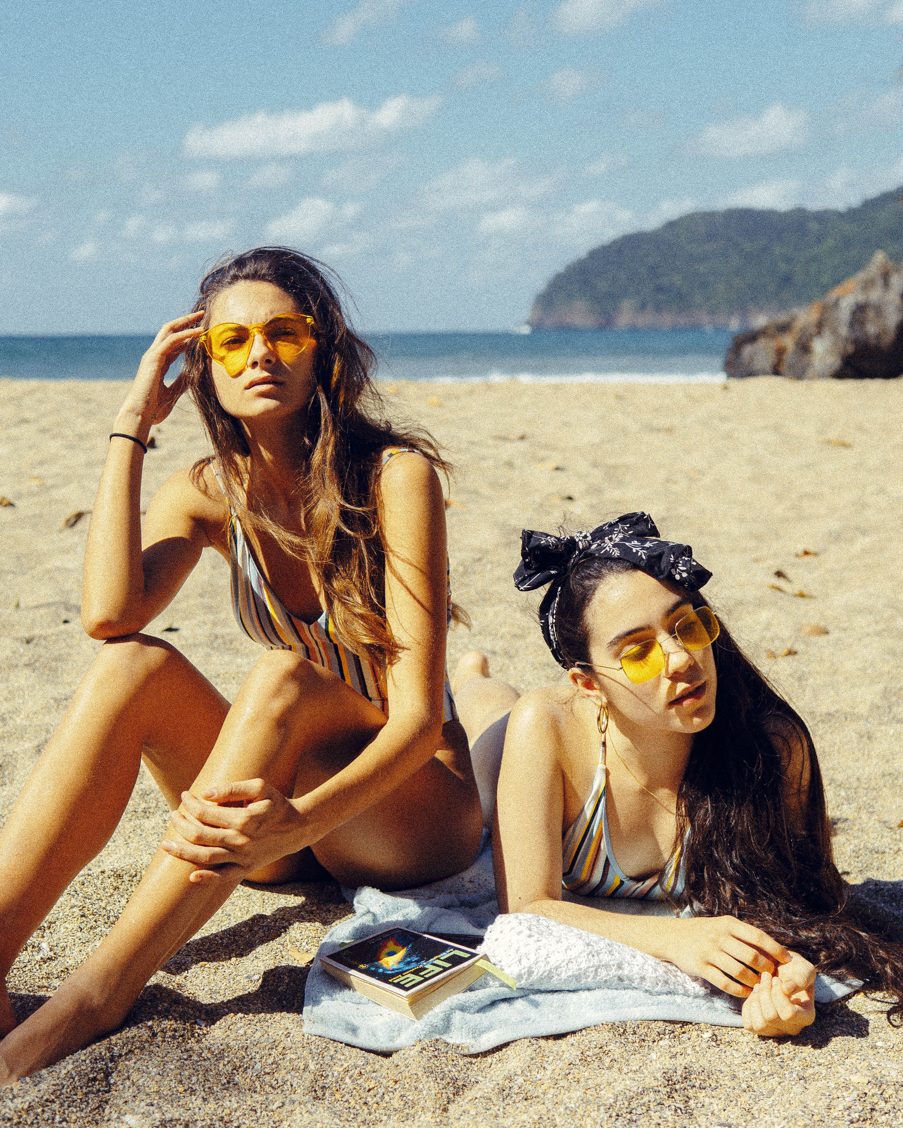 two woman sitting on brown sand