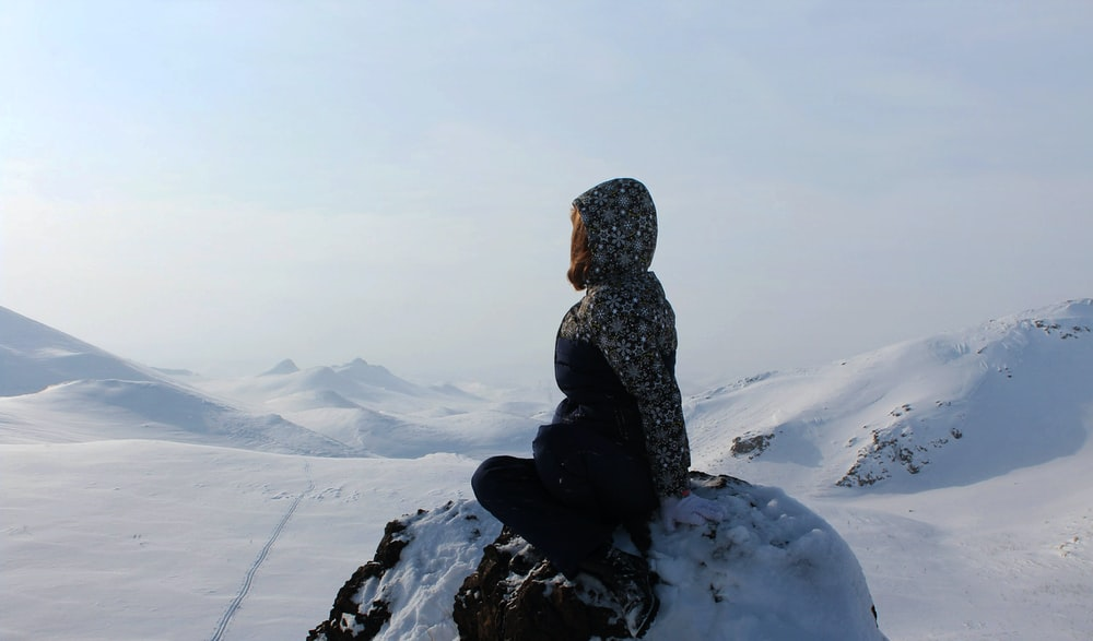 person sitting on rock formation covered by snow