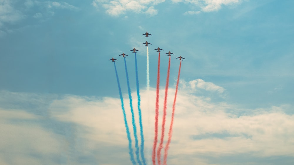 blue, red, and white aircraft in flight creating contrails