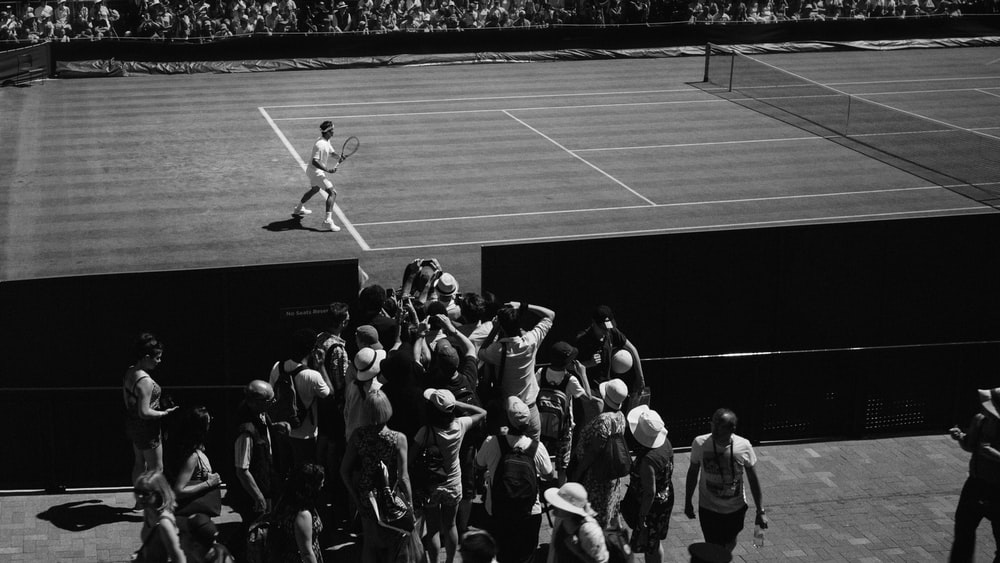 grayscale photo of person playing tennis