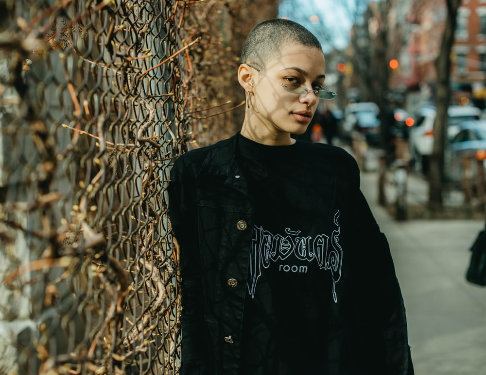 woman wearing black and gray crew-neck sweater leaning on gray chain-link fence during daytime