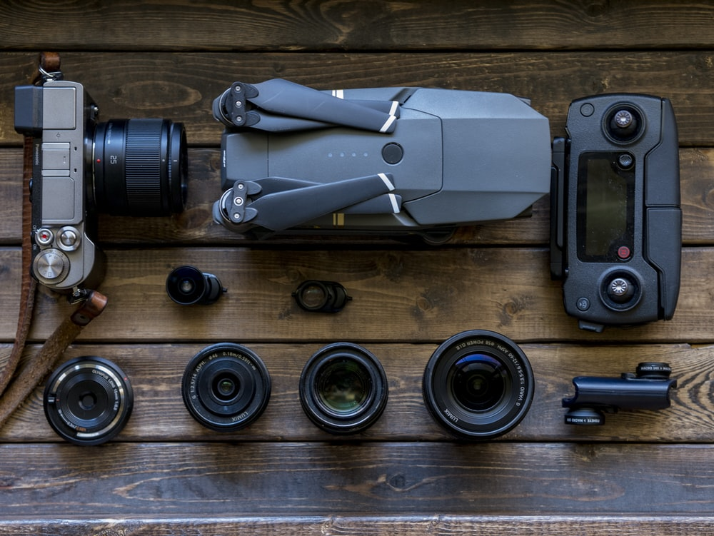 black and grey streaming drone and DSLR camera on brown wooden tabletop