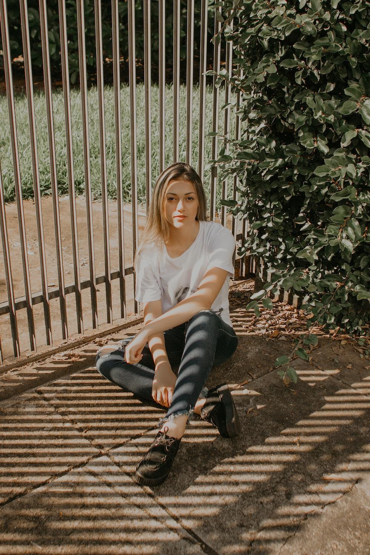 woman sitting beside green bush and gray metal gate