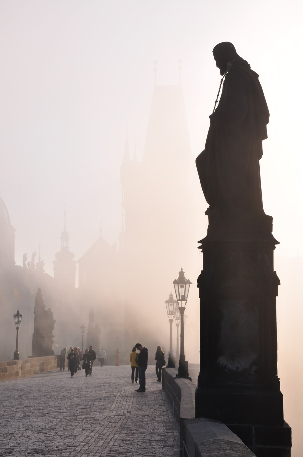 people standing near silhouette of statue