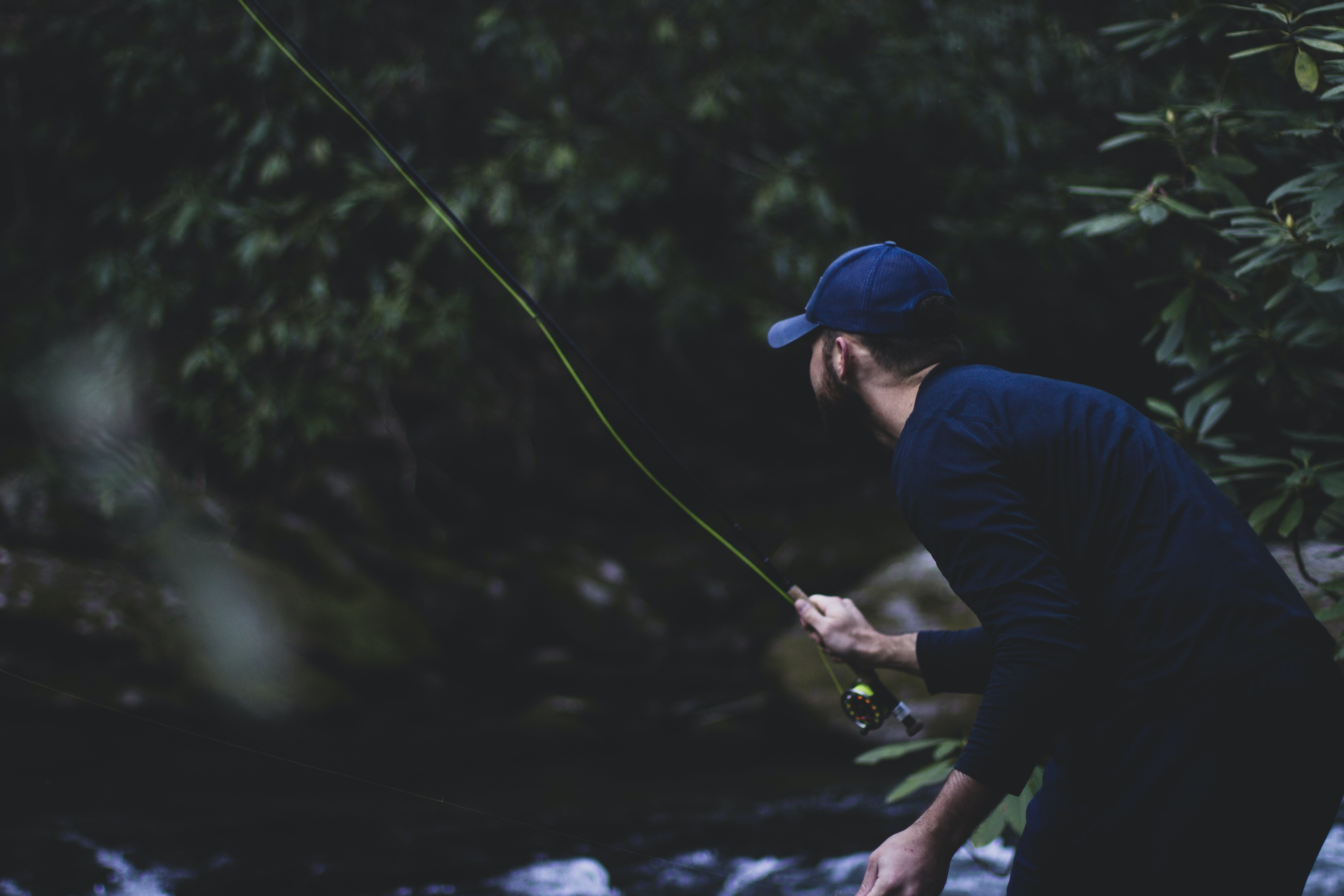 shallow focus photography of man fishing on River