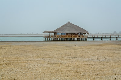 brown wooden hut above water near shore at daytime senegal zoom background