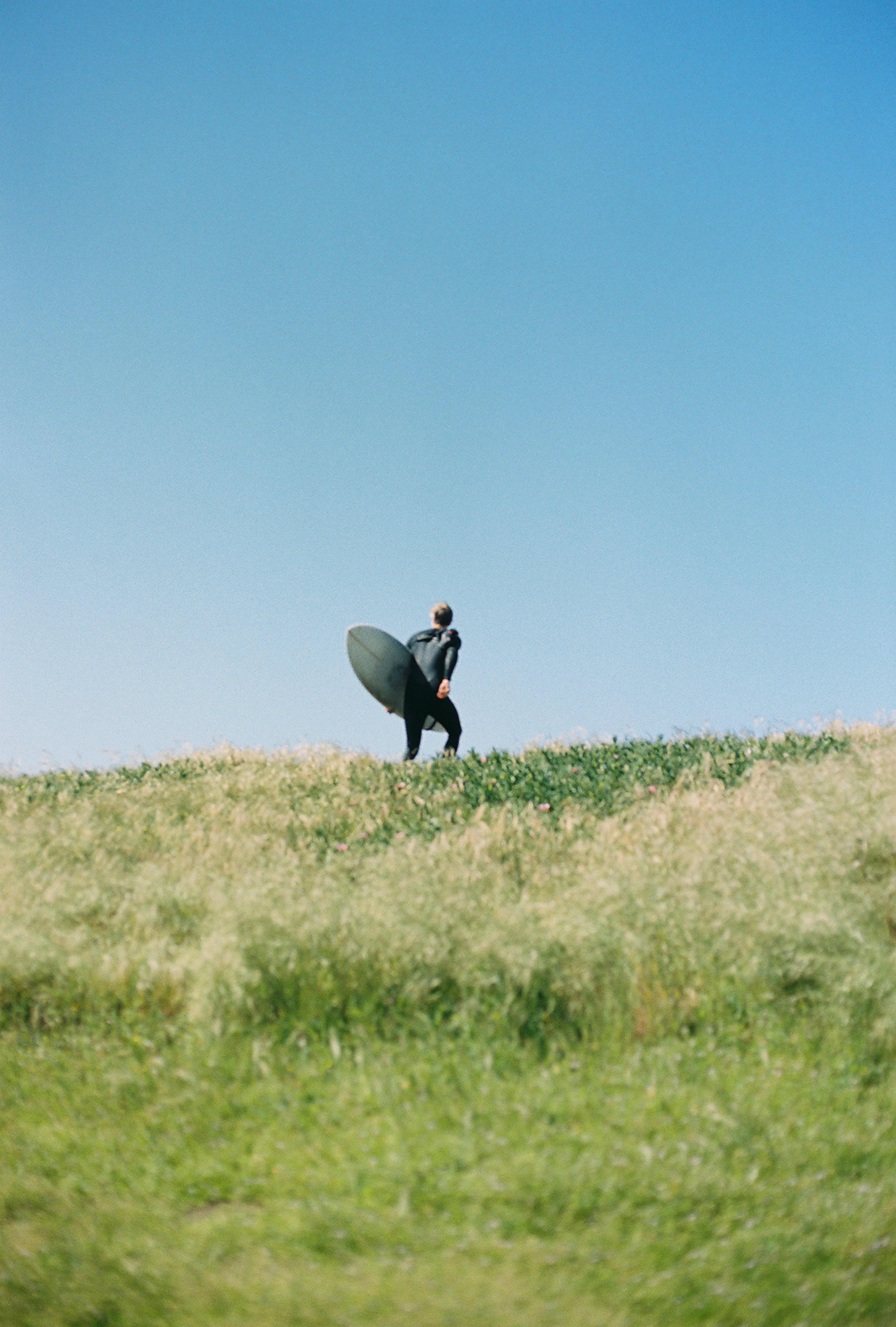 man standing on green grass mountain holding long surfboard