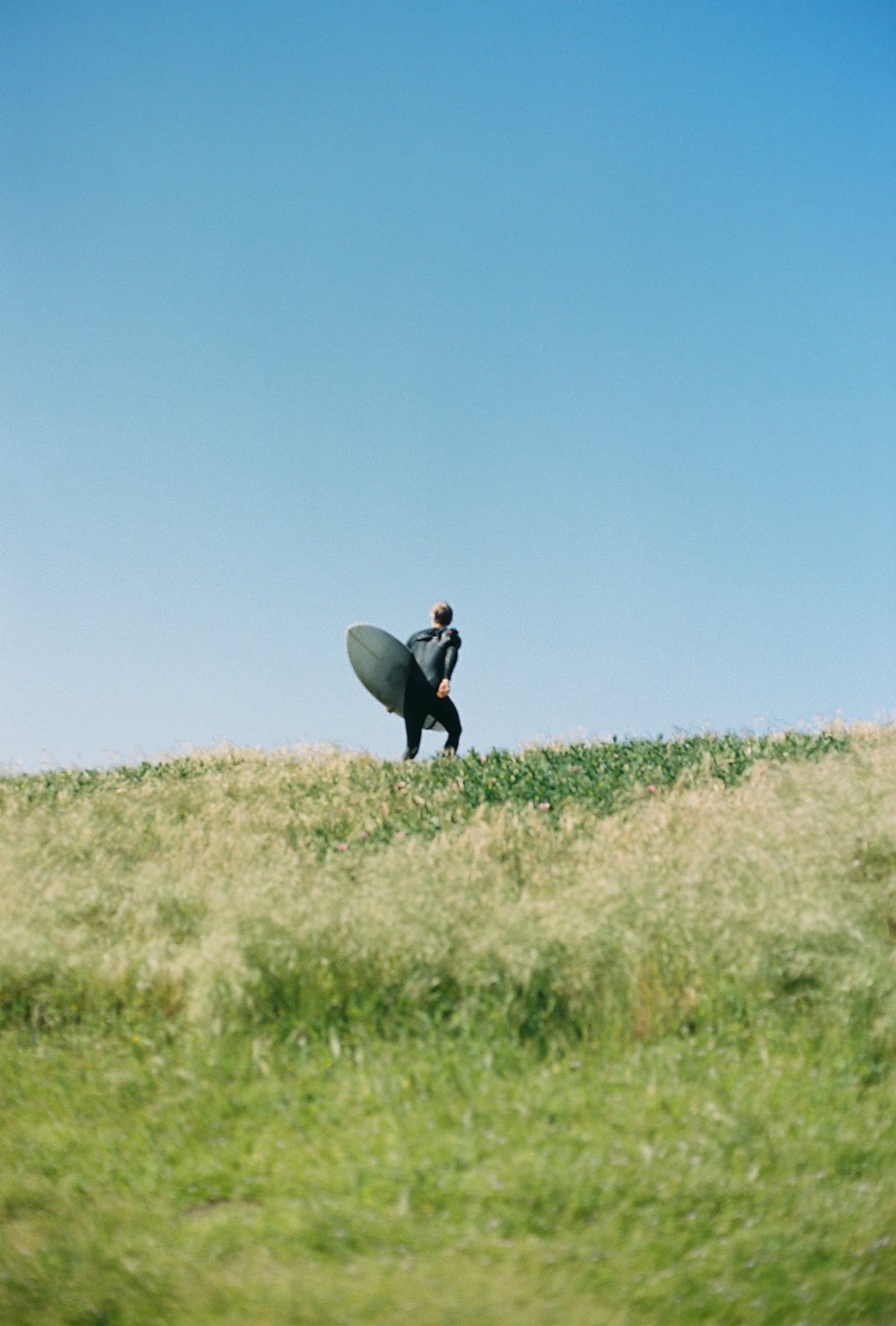 man standing on green grass mountain holding long surfboard