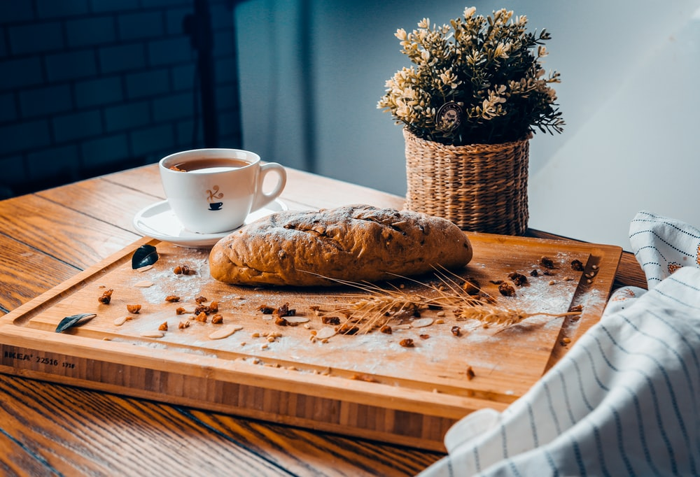 baked bread near cup of coffee both on brown wooden board