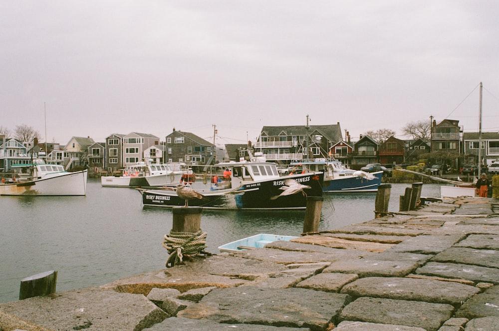 concrete brick floor near sea with boats under grey sky