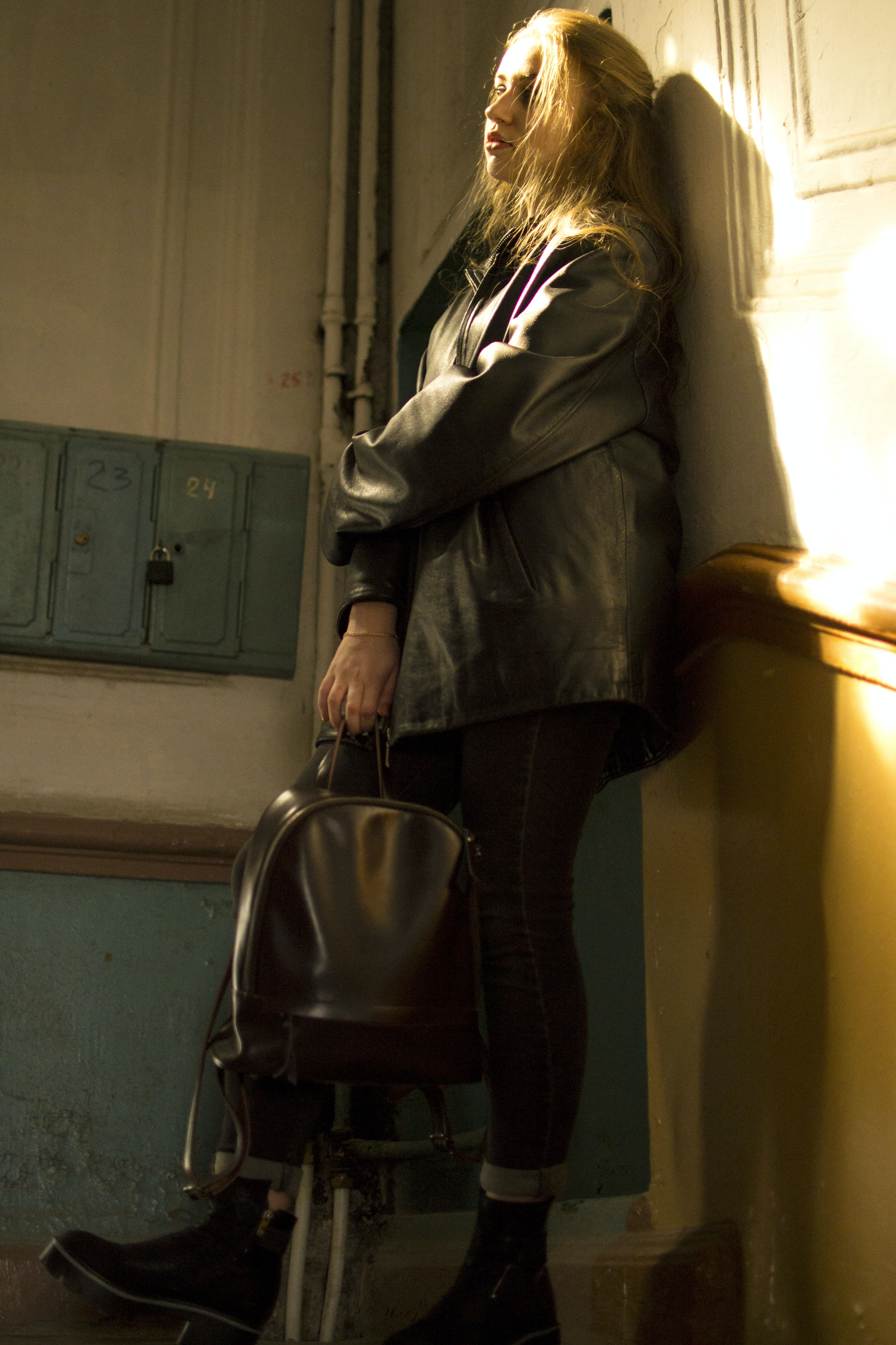woman carrying bag while leaning on wall