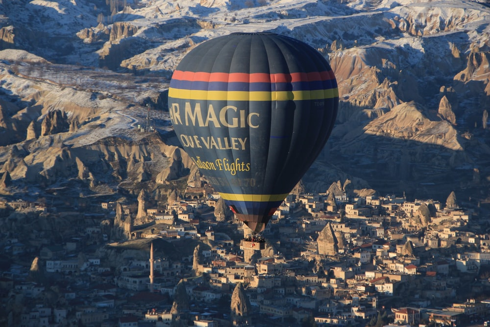 blue, yellow, and red air balloon flying near brown mountain