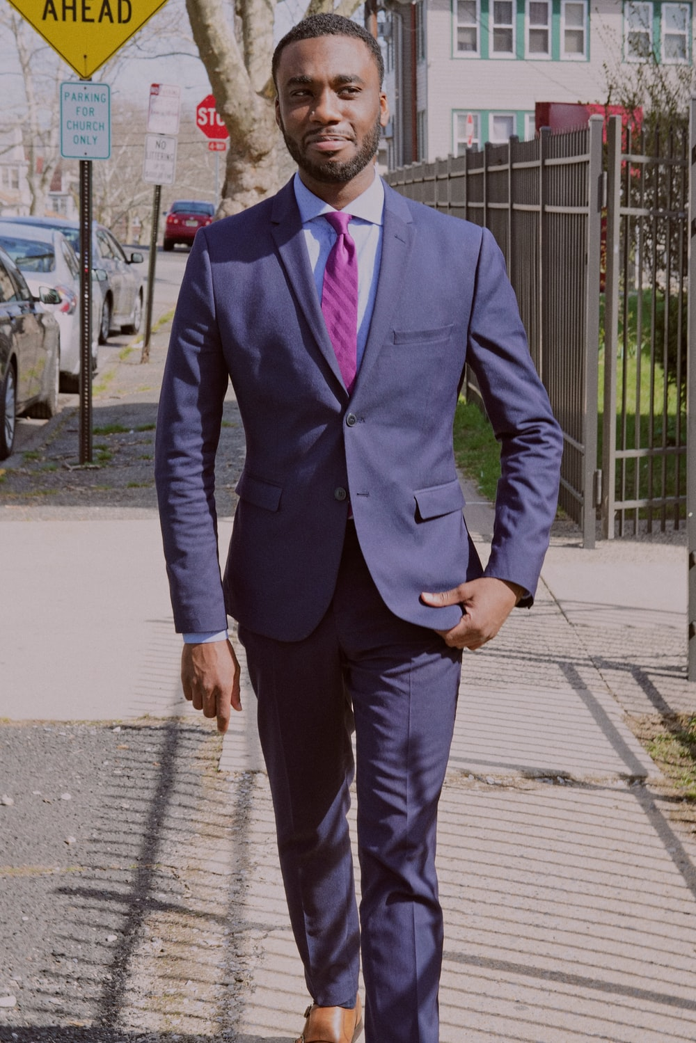 man in blue suit walking on the sidewalk near metal fence and parked vehicle